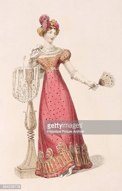A lady wears an early 19th century lownecked dress with short puffed sleeves and a matching turbanlike headpiece She carries an ostrich feather fan