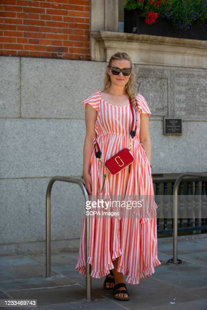 Lady wears Pink city prints dress, Marc Jacobs bag, Birkenstocks sandals, Tom Ford sunglasses during the London Fashion Week digital shows in London.