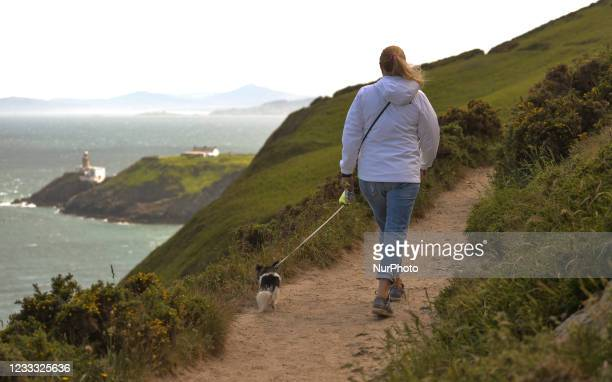 Lady with a small dog walks on the Howth cliff path loop walkon the June Bank Holiday. On Monday, 7 June 2021, in Howth, Dublin, Ireland.