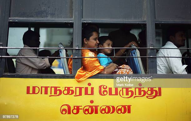 A lady with a young boy on her lap look out the window as they ride the bus on March 20 2010 in Chennai India