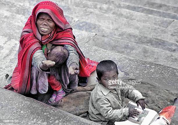 CONTENT] Lady with advanced leprosy cradles her little boy as her older one looks on drawing intermittently Old Delhi India 3/10/2008 glosack
