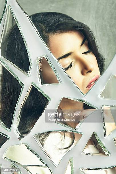 Lady with eyes closed looking sad;  broken mirror