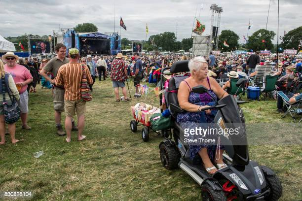 Lady with motorised scooter and baby in tow at Cropredy Festival at Cropredy Oxfordshire on August 11 2017 in Banbury England