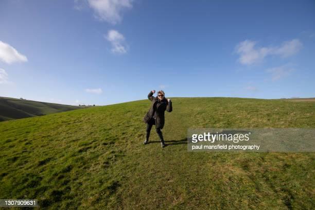 lady with raised fists in field - girl power provérbio em inglês - fotografias e filmes do acervo