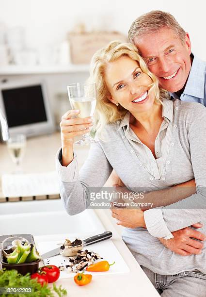 Mann mit Weinglas und Frau umarmt Ihr von hinten