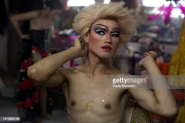 A ladyboy dancer puts on her wig getting into costume backstage at the Chiang Mai Cabaret show September 9 2012 in Chiang Mai Thailand The Cabaret...