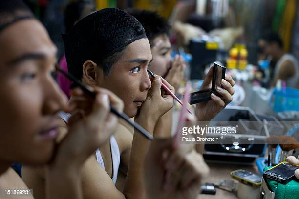 Ladyboy dancers Putter Nicky and Ashi get made up before a performance September 8 2012 in Chiang Mai Thailand The Cabaret show is the only one in...