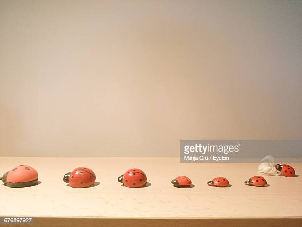 ladybug toys on table against wall - marija mauer stock-fotos und bilder