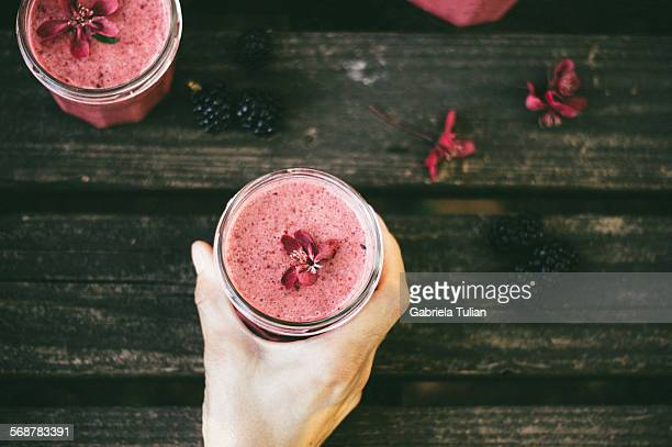 Lady's hand holding a glass of berries smoothie