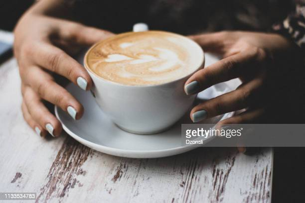 lady's hands holding cup with sth heart-shaped - latte stock pictures, royalty-free photos & images