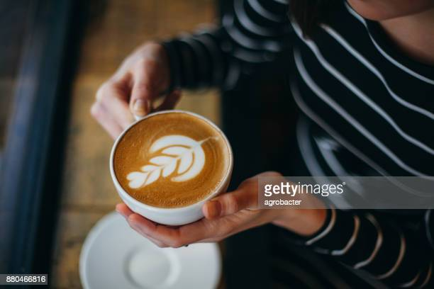 lady's hands holding cup with sth heart-shaped - coffee stock photos and pictures