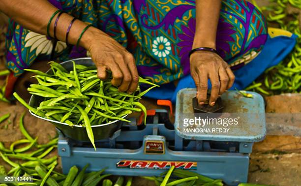 Lady's hands weighing vegetables against weight of 500gms on the weighing scale at the local farmers market.