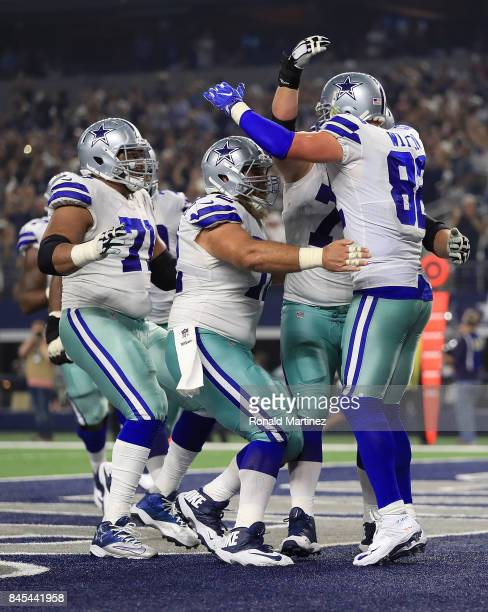 La'el Collins and Travis Frederick of the Dallas Cowboys rush to celebrate the touchdown by Jason Witten in the first half of a game against the New...