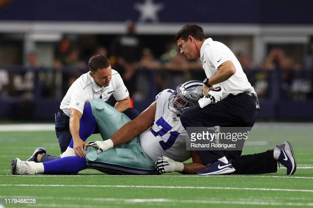 La'el Collins of the Dallas Cowboys is attended to on the field during the game against the Green Bay Packers at ATT Stadium on October 06 2019 in...