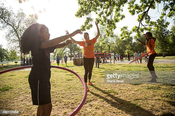 Lael Seals hula hoops with Jennifer Lacy and Tiffany JacksonJones of the Tulsa Shock during the WNBA Cares event at on May 8 2014 at the Mohawk Park...