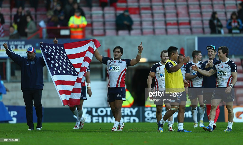 Laelauloto Tagaloa (2L) of USA parades the national flag after his sides 24-16 victory during the Rugby League World Cup Group D match between Wales and USA at the Glyndwr University Racecourse Stadium on November 3, 2013 in Wrexham, Wales.