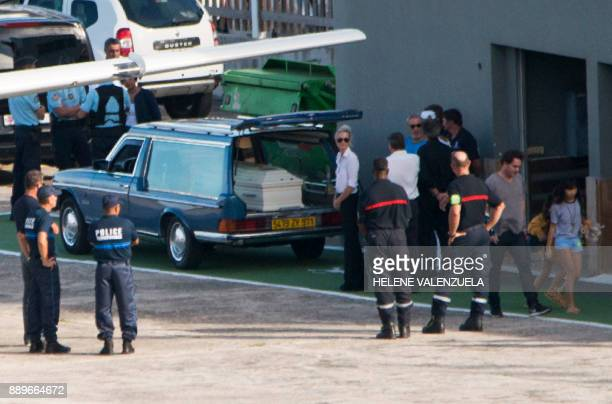 Laeticia Hallyday wife of late French singer Johnny Hallyday and her two daughters Jade and Joy stand by a hearse containing the coffin of late...