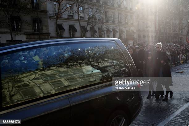 Laeticia Hallyday wife of late French singer Johnny Hallyday her children Jade and Joy stand behind the hearse bearing the coffin of Johnny Hallyday...