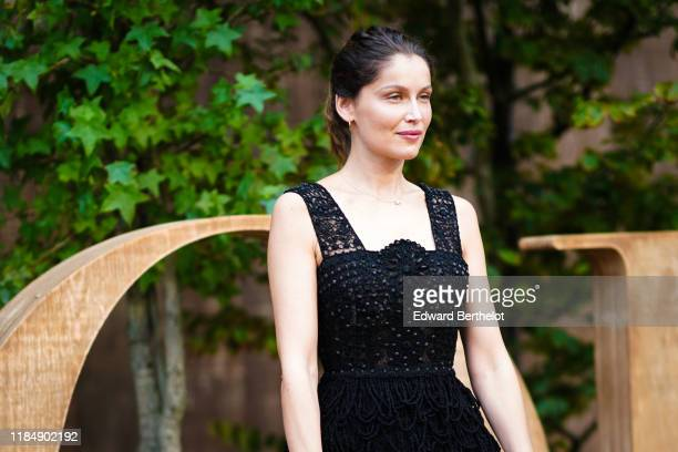 Laetitia Casta wears a black lace mesh dress with embroidery outside Dior during Paris Fashion Week Womenswear Spring Summer 2020 on September 24...