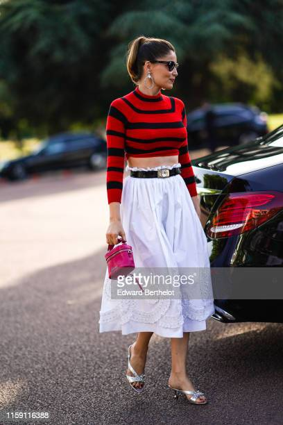 Laetitia Casta wears large earrings, sunglasses, a red and black cropped bare belly top, a belt, a white skirt with embroidery, a pink bag, silver...