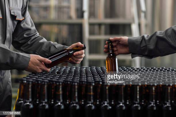 lager making process: unrecognizable factory workers holding bottled beer - brewery stock pictures, royalty-free photos & images