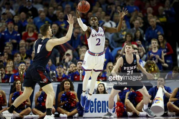 Lagerald Vick of the Kansas Jayhawks and Max Rothschild of the Pennsylvania Quakers reach for a loose ball in the first half during the first round...