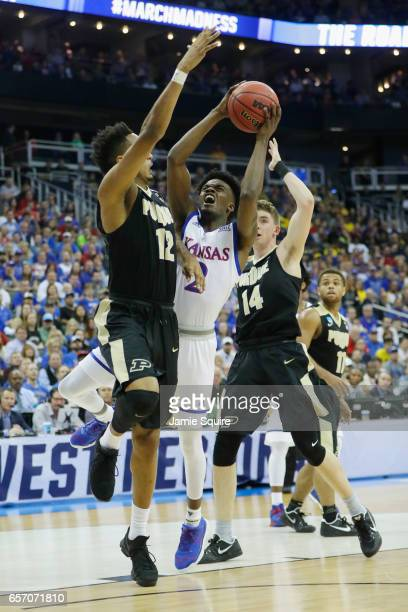 Lagerald Vick of the Kansas Jayhawks drives against Vince Edwards of the Purdue Boilermakers in the first half during the 2017 NCAA Men's Basketball...