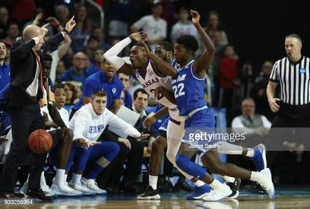 Lagerald Vick of the Kansas Jayhawks fights for a ball headed outofbounds against Khadeen Carrington and Myles Cale of the Seton Hall Pirates in the...