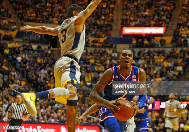 Lagerald Vick of the Kansas Jayhawks is fouled by James Bolden of the West Virginia Mountaineers at the WVU Coliseum on January 15 2018 in Morgantown...