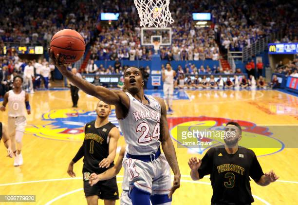 Lagerald Vick of the Kansas Jayhawks scores on a fast break as Skyler Nash and Anthony Lamb of the Vermont Catamounts defend during the game at Allen...