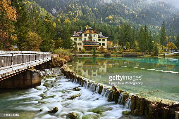 lago di dobbiaco in autumn colors, dolomites, italy - toblach stock photos and pictures