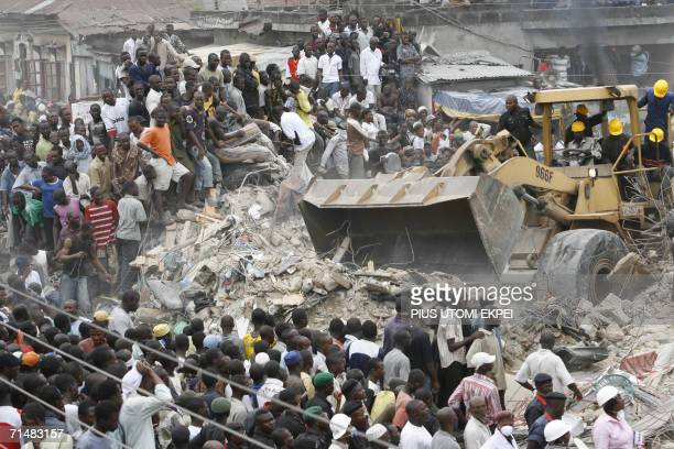 A caterpillar move rubbles from a collapsed building 19 July 2006 as bystanders look on in Lagos Nigerian rescue workers were racing against time...