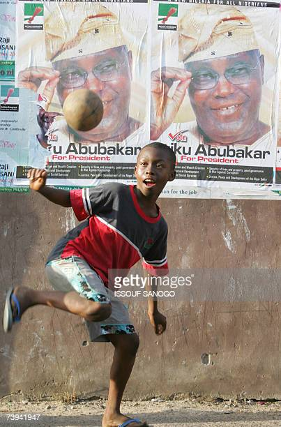 A child plays with a ball backdropped by posters of presidential candidate Atiku Abubacar 21 April 2007 in Lagos on the first day of polling to...