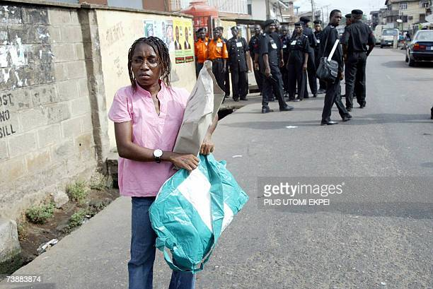 A female INEC official waites for police escorts standing behind to lead her to a polling station at Ilupeju district in Lagos Saturday 14 April 2007...