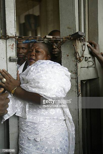 A female party delegate squeezes through a narrow passage created by security operatives in Tafawa Balewa Square in Lagos 20 December 2006 where...