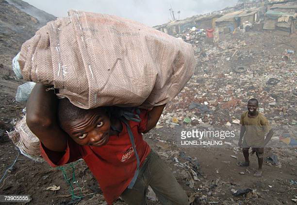 A man carries a load of scrap through a dump 17 April 2007 in Lagos Olusosun Land Fill Site is Nigeria's largest rubbish dump dealing with 2400...
