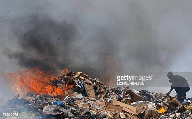 A man sifts through rubbish at a dump 17 April 2007 in Lagos Olusosun Land Fill Site is Nigeria's largest rubbish dump dealing with 2400 metric tons...