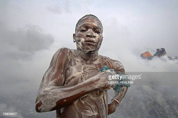 A man soaps himself on a dump after a day's work 17 April 2007 in Lagos Olusosun Land Fill Site is Nigeria's largest rubbish dump dealing with 2400...
