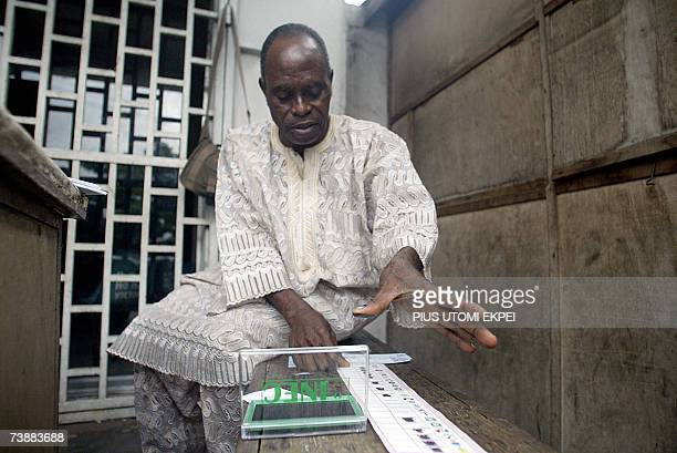 A man tries to thumb print on a voters card at a polling station in Lagos 14 April 2007 Nigerians voted today in elections for governors and...