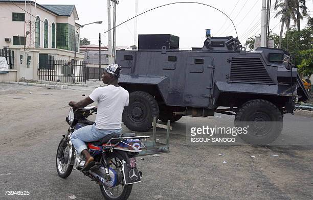 A motorcyclist rides past a Nigerian tank deployed at the Independent Electoral Commission headquarters 22 April 2007 in Lagos on the eve of the...