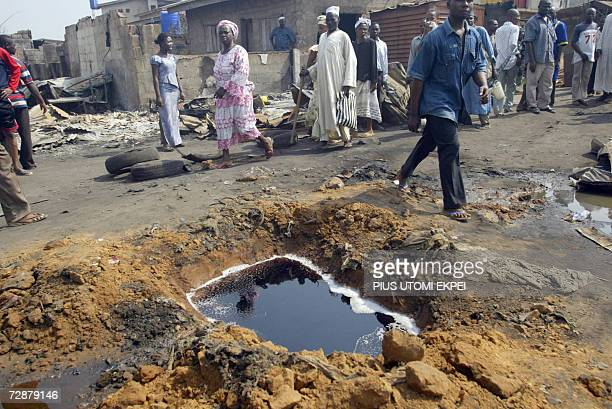 People walk past exposed fuel licking from a burst oil pipeline at the scene of the oil pipeline fire in Abule Egba on the outskirts of Lagos 27...