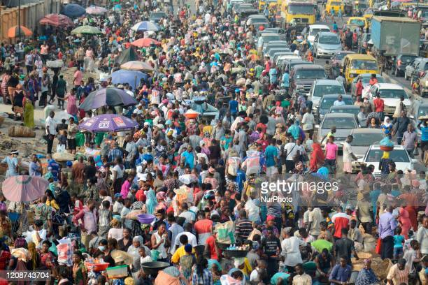 Lagos residents, despite social distancing order, cluster at Oke-Odo Market, Lagos Nigeria on Monday March 30, 2020 for last minute shopping. Federal...