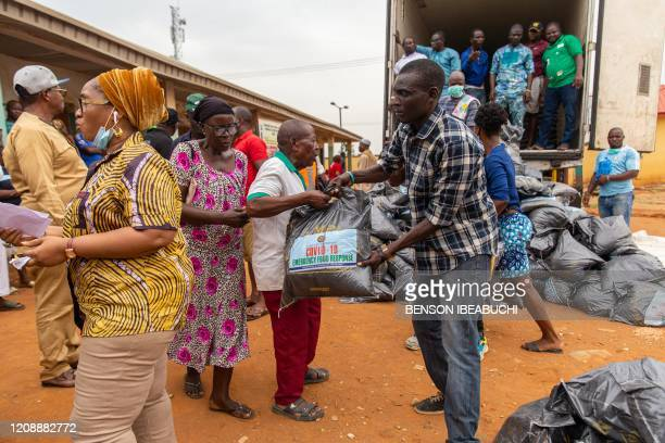 Lagos State Officials hand out the food relief bags to people of the Agbado and OkeOdo LCDA community in Lagos on April 1 2020 More than 20 million...