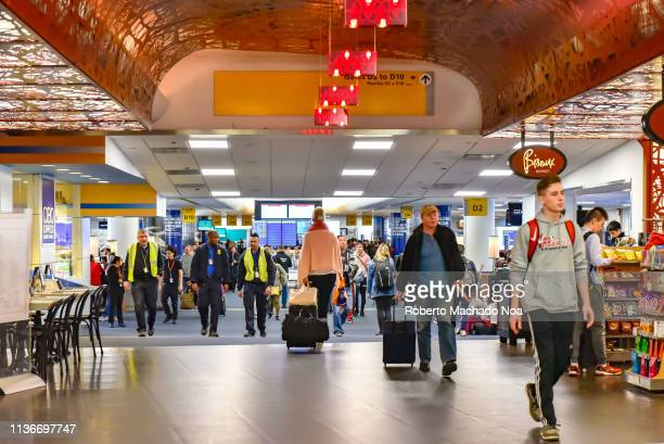 LaGuardia Airport passengers walk the corridor with carry on luggage and backpacks
