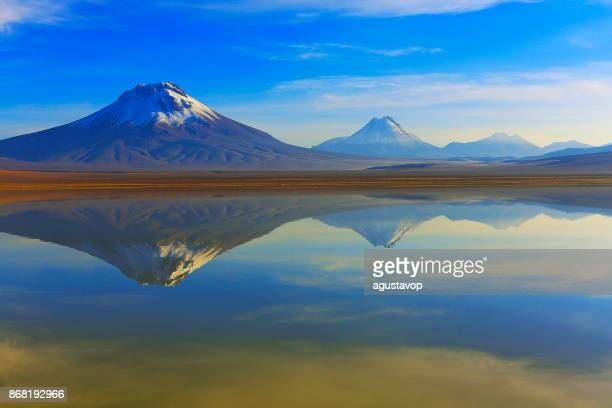 laguna lejia – dramatic lejia lake mirrored reflection at gold colored sunrise dawn, snowcapped lascar volcano and volcanoes, idyllic atacama desert, volcanic landscape panorama – san pedro de atacama, chile, bolívia and argentina border - volcanic terrain stock photos and pictures