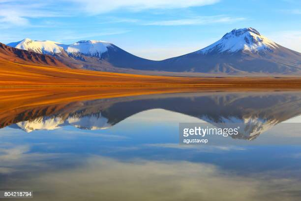 laguna lejia, lake lejia reflection mirrored at dramatic gold colored sunrise, volcanoes and idyllic atacama desert altiplano with lascar volcano, volcanic landscape panorama – san pedro de atacama, chile, bolívia and argentina border - ecuador stock pictures, royalty-free photos & images