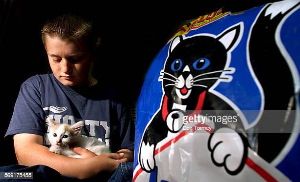 """Laguna Niguel––John Pankowski holds """"Peachy"""" one of nine kittens from two different cats in his garage in Laguna Niguel. The Pankowski children with..."""