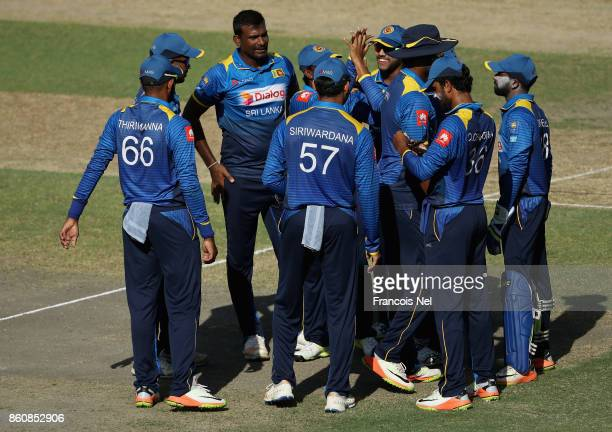 Lahiru Gamage of Sri Lanka celebrates with teammates after dismissing Ahmed Shehzad of Pakistan during the first One Day International match between...