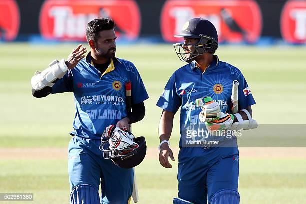 Lahiru Thirimanne and Dinesh Chandimal both of Sri Lanka walk from the field after winning the third One Day International match between New Zealand...