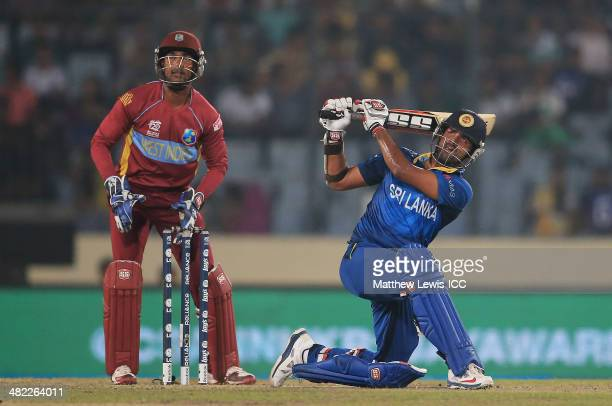 Lahiru Thirimanne of Sri Lanka hits a six as Denesh Ramdin of the West Indies looks on during the ICC World Twenty20 Bangladesh 2014 Semi Final match...